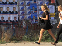 Girls walk past election campaign posters of candidates running for deputies ahead of parliamentary elections in Russia.-- Reuters photo