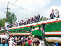 Passengers are seen standing on the rooftop of a train at Shaheed M Mansur Ali railway station in Sirajganj as homebound people get on and off the train on Friday. — New Age photo