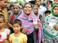 Relatives, holding photographs, anxiously wait for their dear and near ones who till Sunday remained missing in the Tongi factory fire, which claimed at least 29 people.  — Sanaul Haque